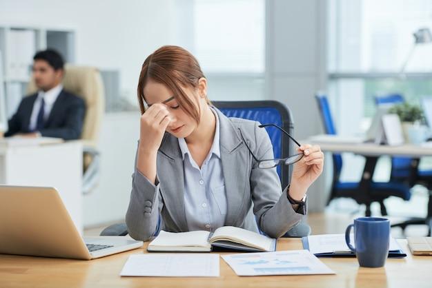 Plano medio de la joven mujer asiática sentada en el escritorio en la oficina y frotándose la nariz Foto gratis