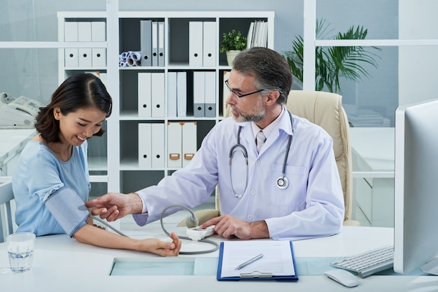 Plano medio del médico que controla la presión arterial del paciente femenino Foto gratis