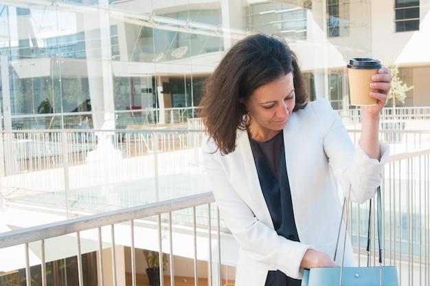 Plano medio de mujer mirando algo en bolsa, sosteniendo café Foto gratis