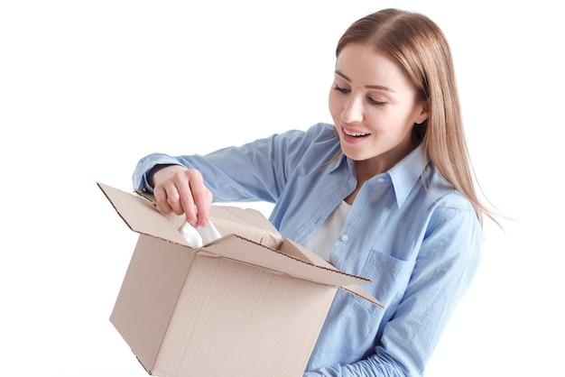 Plano medio de una mujer mirando dentro de un paquete de entrega Foto gratis