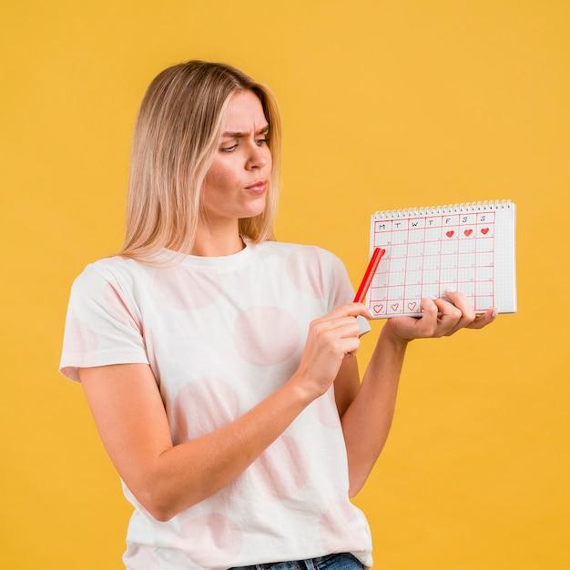 Plano medio de mujer mostrando el calendario del período Foto gratis
