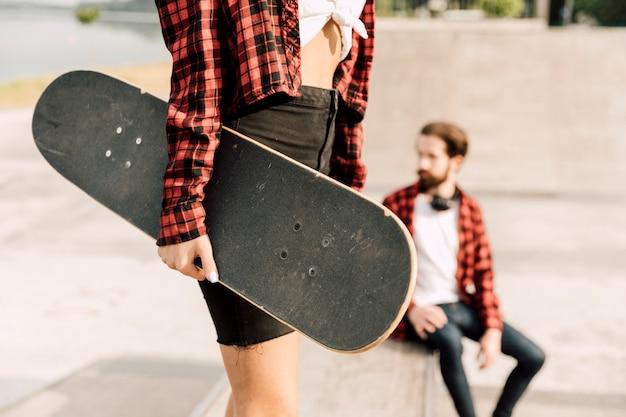 Plano medio de mujer sosteniendo patineta Foto gratis
