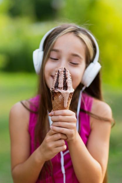 Plano medio de niña con cono de helado Foto gratis