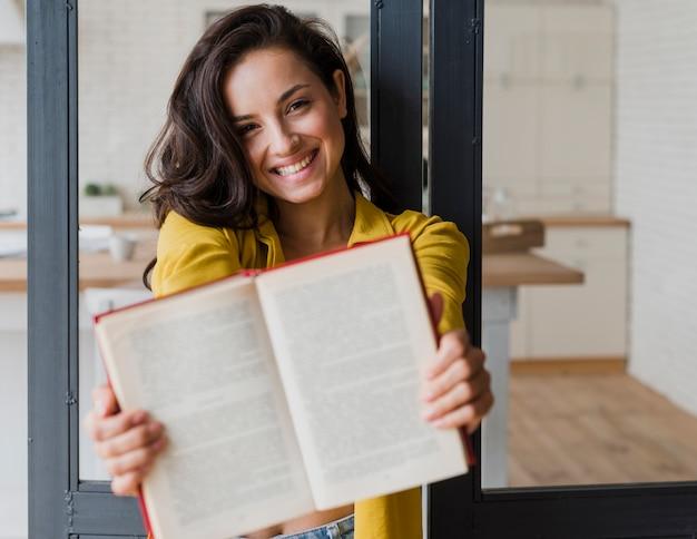 Plano medio niña feliz mostrando libro a la cámara Foto gratis