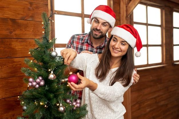 Plano medio pareja feliz decorando el árbol de navidad Foto gratis