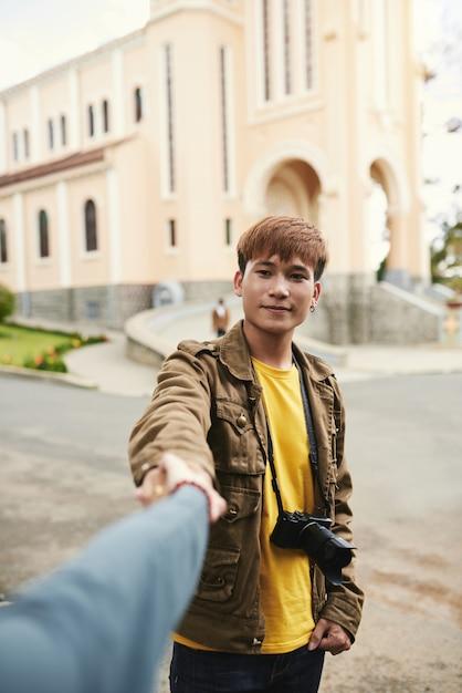 Plano medio retrato de un chico asiático con cámara de fotos de la mano de una mujer irreconocible Foto gratis