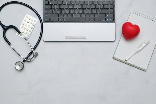 Plano con mesa de escritorio médico con estetoscopio, cuaderno, material de oficina y espacio de copia Foto Premium