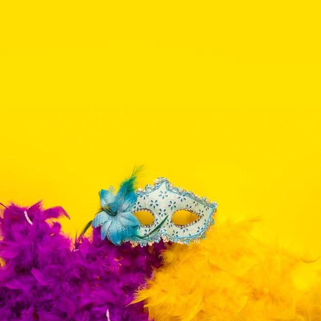 Plano pone coloridos objetos de carnaval sobre fondo amarillo con espacio de copia Foto gratis
