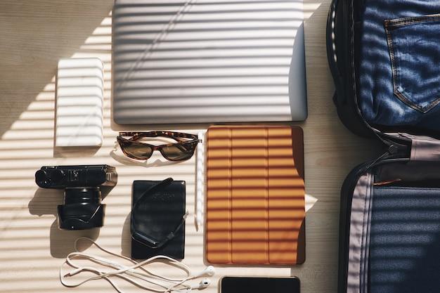 Plano superior de dispositivos electrónicos y maleta sobre la mesa, listo para un viaje de negocios Foto gratis