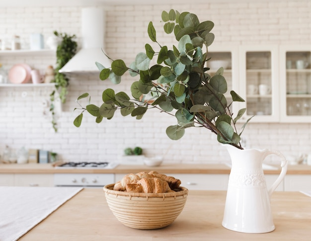 Planta decorativa sobre mesa en luminosa cocina moderna. Foto gratis