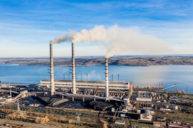 Planta de electricidad industrial de carbón pesado con tuberías y humo en blanco y negro Foto Premium