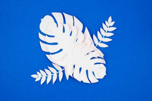 Plantas tropicales en el estilo de papel cortado sobre fondo azul. Foto gratis
