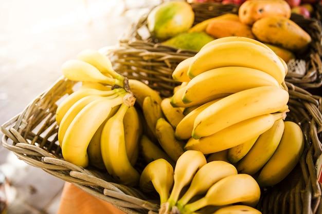 Plátanos maduros amarillos en cesta de mimbre en la tienda del mercado de frutas Foto gratis