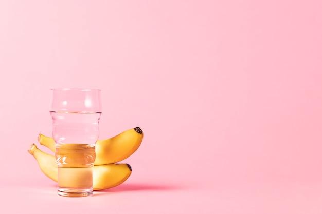 Plátanos y vaso de agua copia espacio Foto gratis