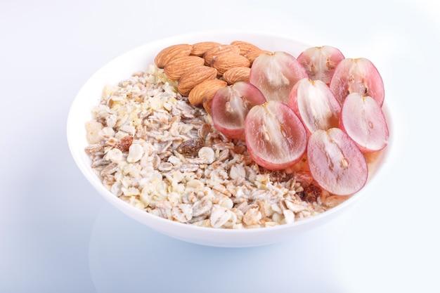 Un plato con almendras muesli uvas rosas aislado sobre un fondo blanco. Foto Premium