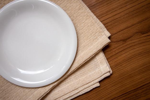 El plato blanco se coloca sobre un mantel crema sobre la mesa de madera. Foto Premium