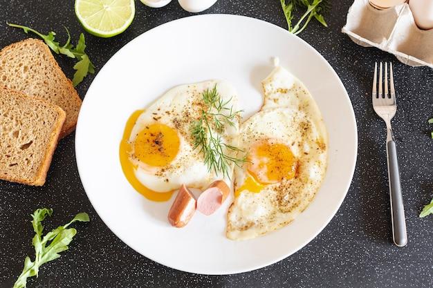 Plato blanco con huevos fritos y pan sobre una mesa negra Foto gratis