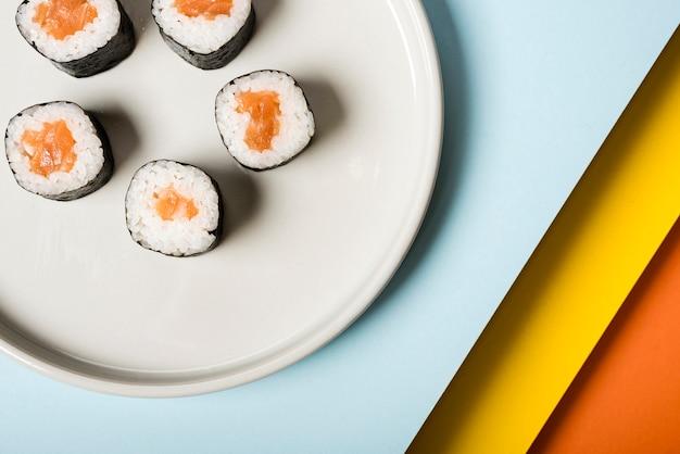 Plato blanco minimalista con rollos de sushi. Foto gratis