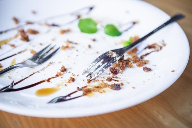 Plato blanco y restos de comida después de comer. Foto Premium