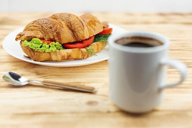 Plato blanco con un sandwich y una taza de café sobre una mesa de madera Foto gratis