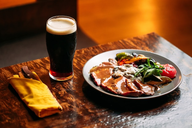 Plato de carne y verduras cocidas con un vaso de cerveza oscura en la mesa del bar Foto Premium
