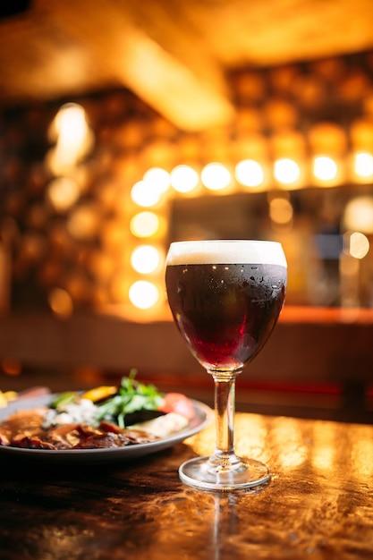 Plato de carne y verduras con un vaso de cerveza oscura con luces borrosas Foto Premium