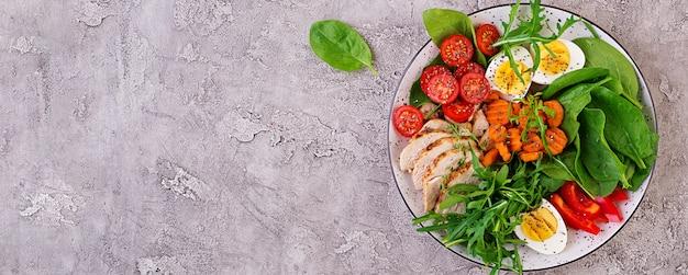 Plato con una comida de dieta ceto. tomates cherry, pechuga de pollo, huevos, zanahoria, ensalada con rúcula y espinacas. keto almuerzo. vista superior Foto gratis