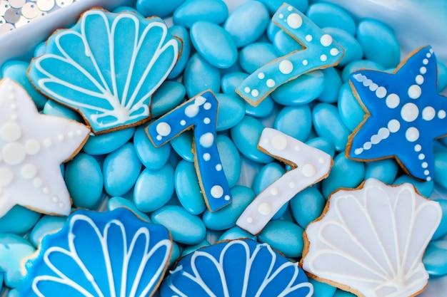 Plato de concha blanca llena de dulces de chocolate con glaseado azul, galletas como conchas, estrellas y número siete Foto Premium
