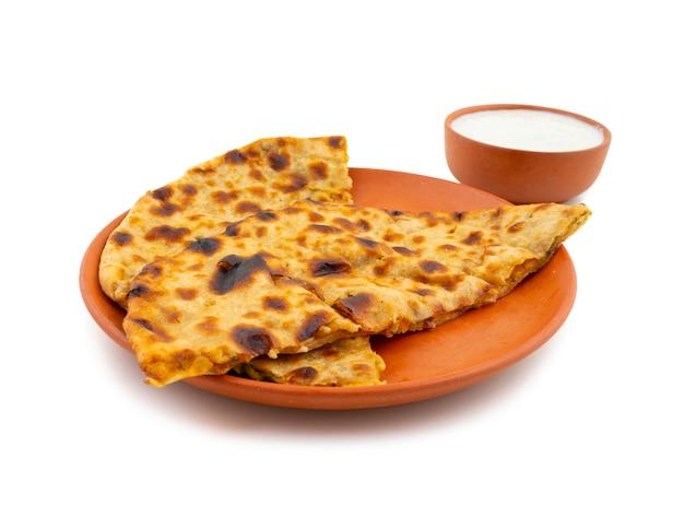 Plato de desayuno indio aloo paratha servido con cuajada sobre fondo blanco. Foto Premium