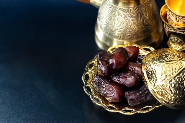 Plato dorado con frutos de palmera datilera o kurma. concepto de ramadan kareem. de cerca. Foto Premium
