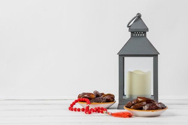 Plato de fechas jugosas con cuentas de oración rojas y una vela en un soporte de linterna sobre fondo blanco Foto gratis