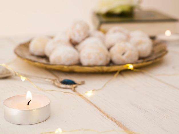 Plato de galletas desenfocado con vela y corán. Foto gratis