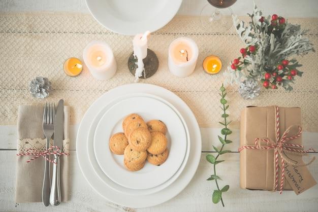 Plato de galletas y presente en la mesa con adornos navideños Foto gratis