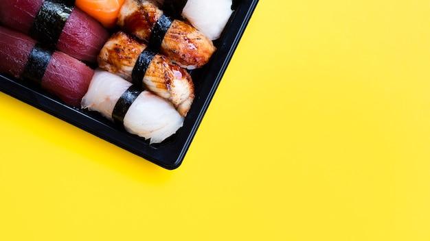 Plato grande de sushi negro sobre un fondo amarillo Foto gratis