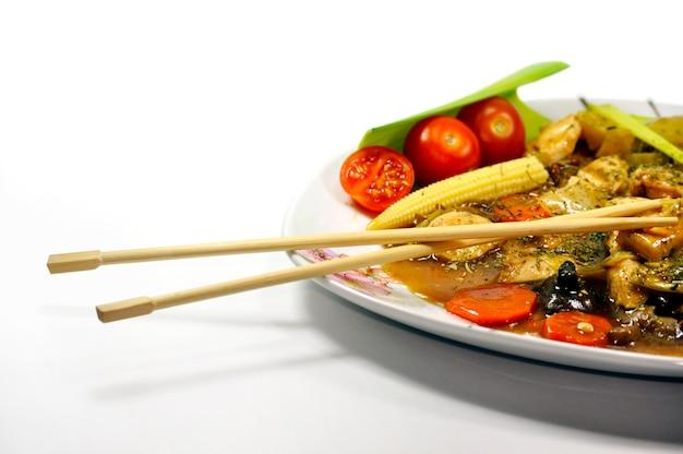 Plato con hortalizas y palillos chinos Foto gratis