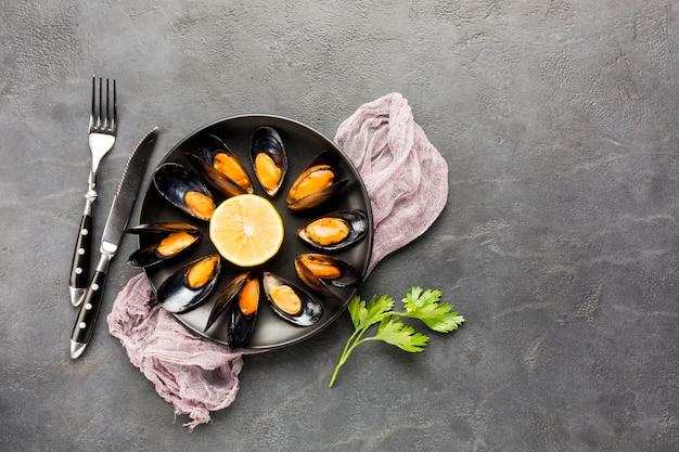 Plato de mejillones cocido plano con cubiertos. Foto gratis