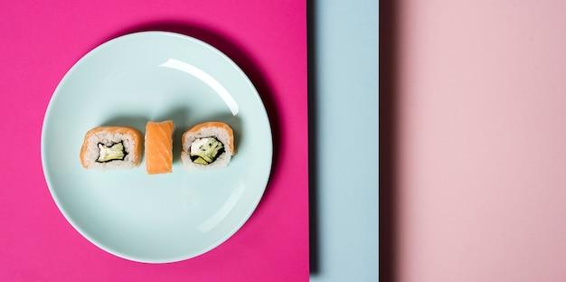 Plato minimalista con rollos de sushi y capas de fondo. Foto gratis