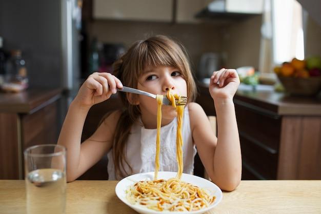 Plato de pasta servido a niña juguetona Foto gratis