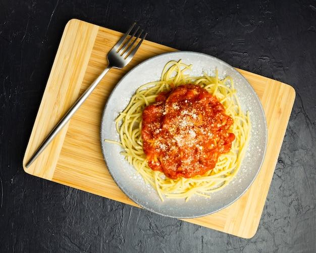 Plato de pasta sobre tabla de cortar con tenedor Foto gratis