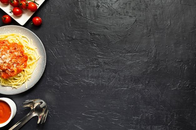 Plato de pasta con tomates en pizarra Foto gratis