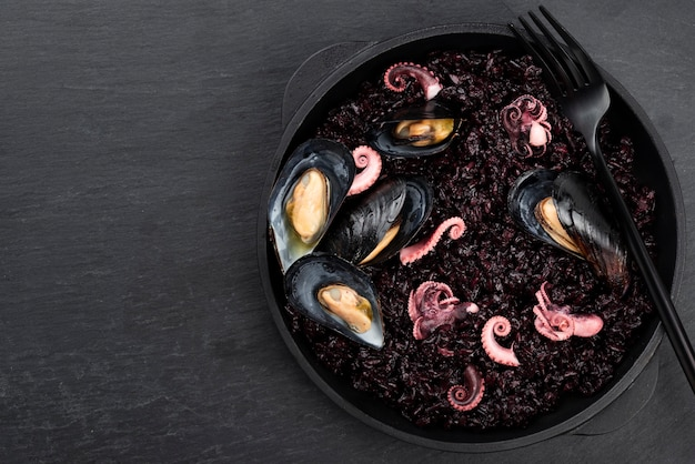 Plato plano de plato con pasta negra y mejillones Foto gratis