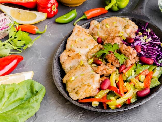 Plato con plato de carne junto a verduras y limones. Foto gratis