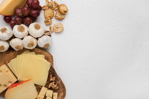 Plato de queso con bulbo de ajo; uvas rojas; pan y nuez contra fondo concreto Foto gratis