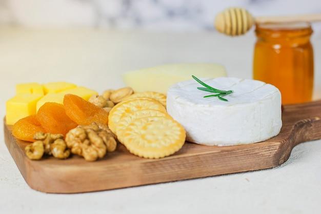 Plato de queso, queso camembert, romero, galletas, albaricoque seco y nueces Foto gratis