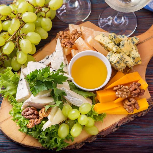 Plato de queso servido con vino blanco, uva y nueces. Foto Premium