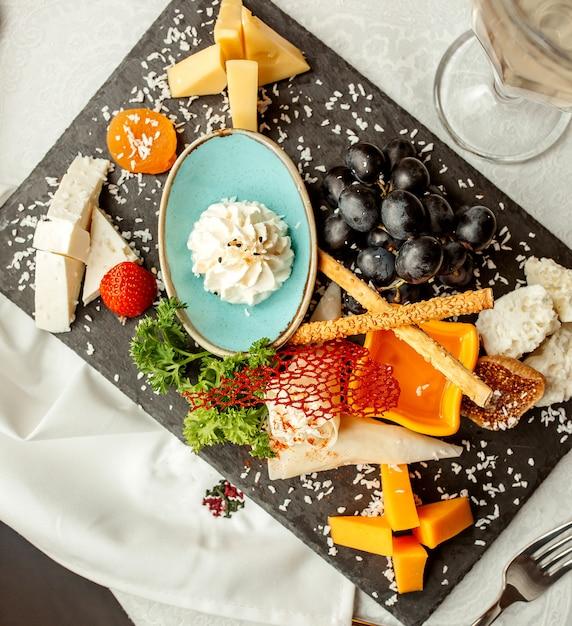 Plato de queso y uva con galletas Foto gratis