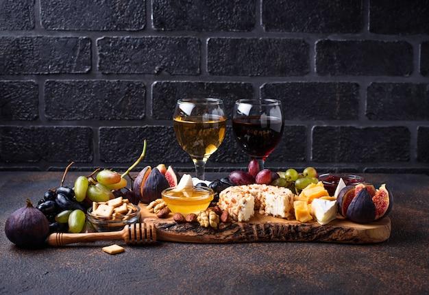 Plato de queso con uvas y vino. Foto Premium