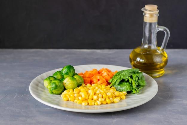 Plato con repollo, zanahorias, maíz y espinacas. Foto Premium