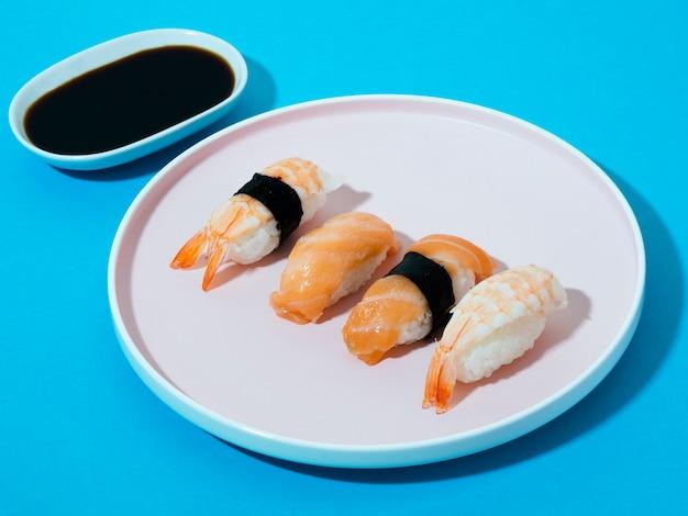 Plato de sushi blanco y tazón de salsa de soja sobre un fondo azul. Foto gratis
