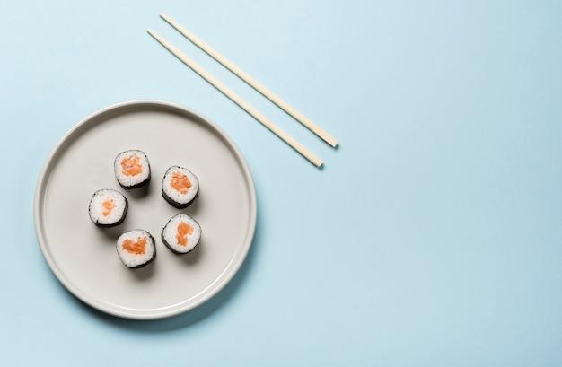 Plato de sushi japonés minimalista sobre fondo azul. Foto gratis